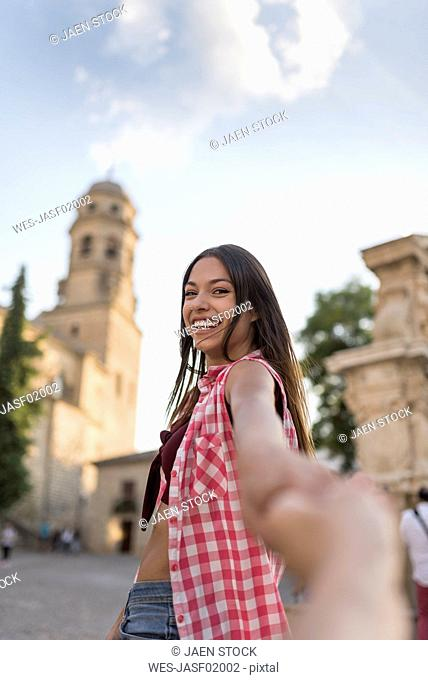 Spain, Baeza, portrait of happy young woman holding hands in the city