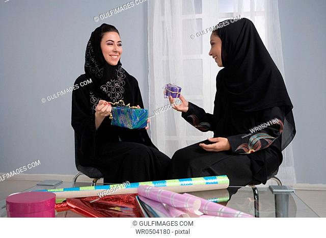 Two arab women wrapping gifts together