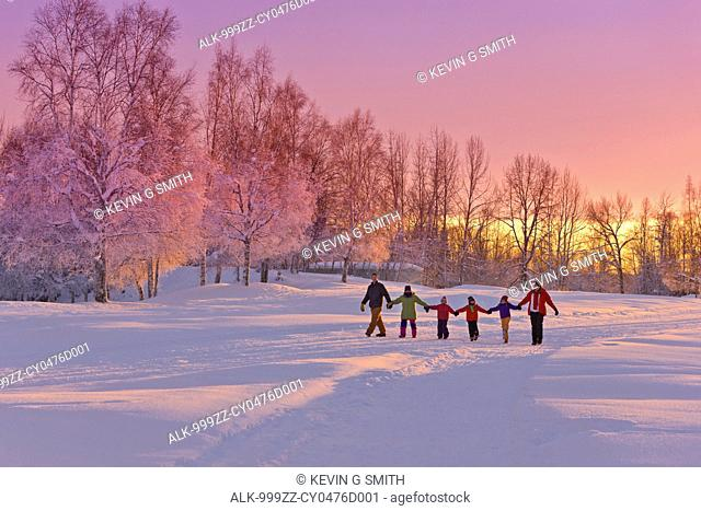 Family group, holding hands, walk on a snow path at sunset with a birch forest in the background, Russian Jack Springs Park, Anchorage, Southcentral Alaska