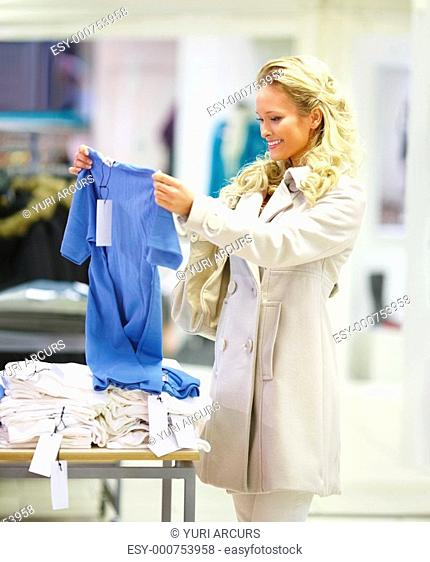 Photo of a girl in the clothing store holding a blue top and looking at it with a smile