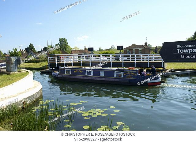A colourful narrowboat passes through the swing bridge at Purton on the Gloucester & Sharpness Canal at Purton in summer sunshine, Gloucestershire, UK