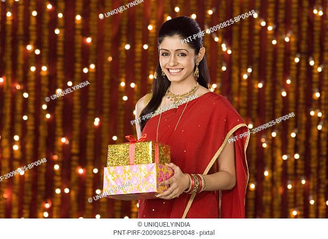 Woman holding Diwali gift and smiling