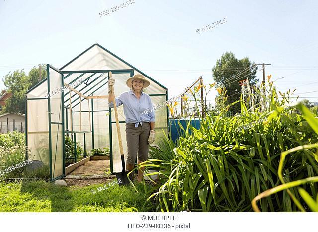 Portrait confident senior woman with shovel at greenhouse