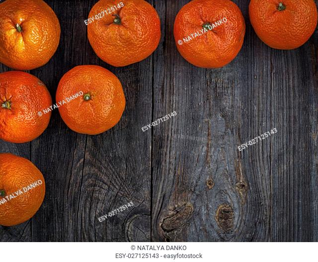 Orange mandarins on the gray old wooden surface, top view, an empty space in the middle