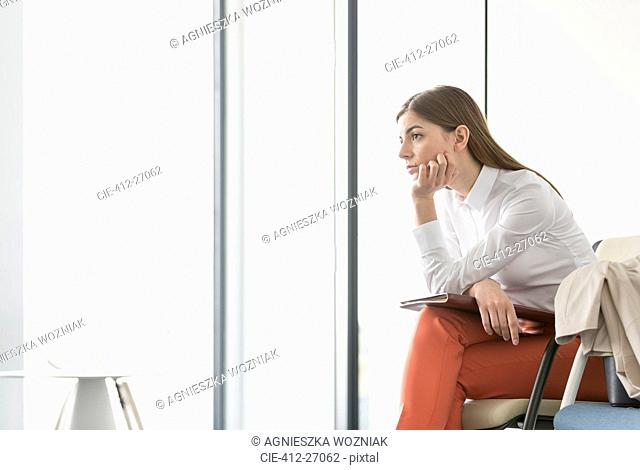 Pensive brunette businesswoman looking out office window with hand on chin
