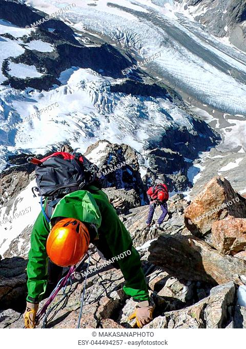 Several montan climbers rappelling of a high alpine summit with a wild and torn glacier far below them