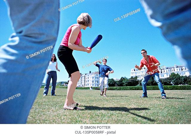 A group playing baseball in a park
