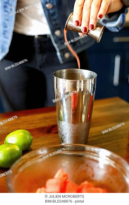Woman pouring liquid into cocktail shaker