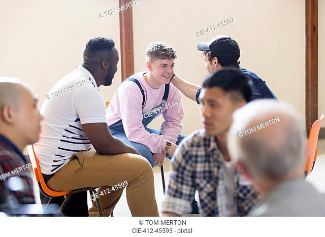 Men talking, comforting in group therapy