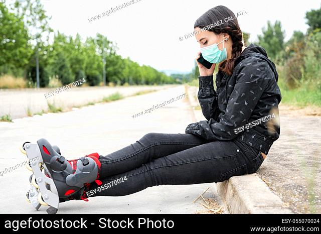 Woman in protective face mask on roller skating pause, sitting on the street and using mobile phone during coronavirus pandemic outbreak