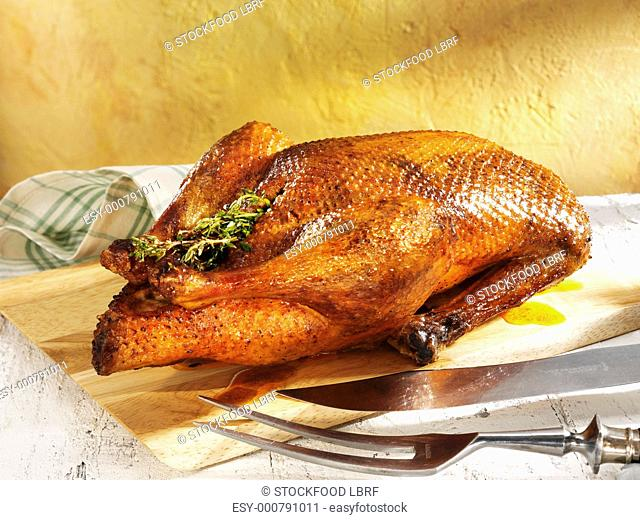 Roast duck with carving cutlery