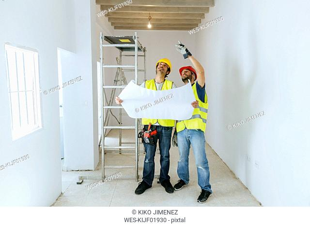 Two workers talking, holding the construction plane