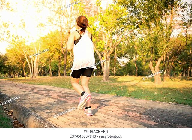 Young woman running in wood, training and exercising for trail run marathon endurance in morning sunrise. Fitness healthy lifestyle concept