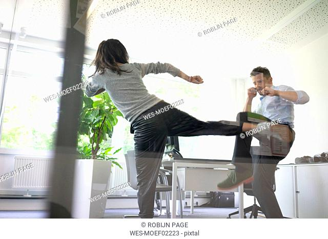 Businessman and businesswoman fighting in office