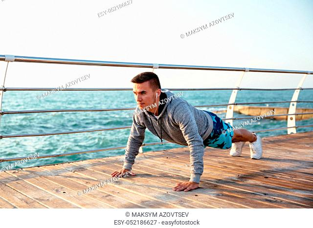 Outdoor photo of a sportive man in headphones doing push-ups exercises, during workout on quay, near the ocean