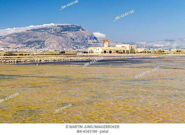 Windmill behind Culcasi saltworks, Natural Reserve of saltworks with salt marshes, Via del Sale, Salt Road, Nubia, Province of Trapani, Sicily, Italy