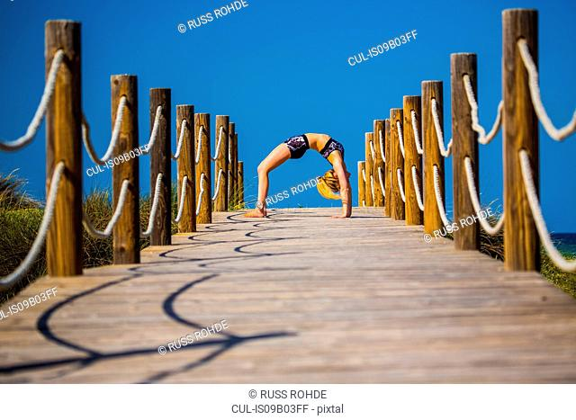 Young woman on wooden pathway, exercising, bent over backwards