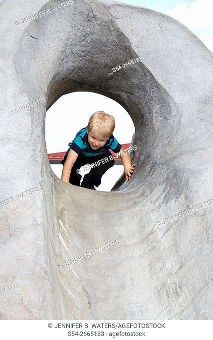 A boy plays in a concrete slide at a playground in Spokane, Washington, USA