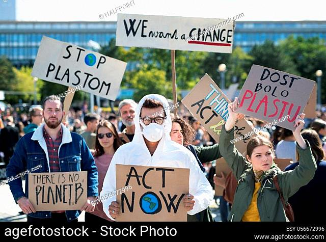 A people with placards and protective suit on a global strike for climate change