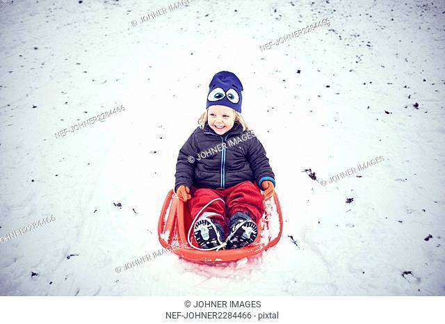 Smiling girl sliding on toboggan
