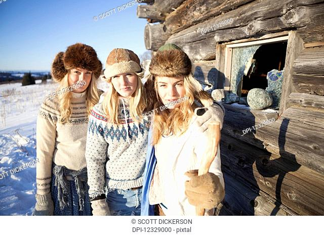 Portrait Of Three Girls Standing By A Log Cabin Wearing Fur Hats; Homer, Alaska, United States Of America