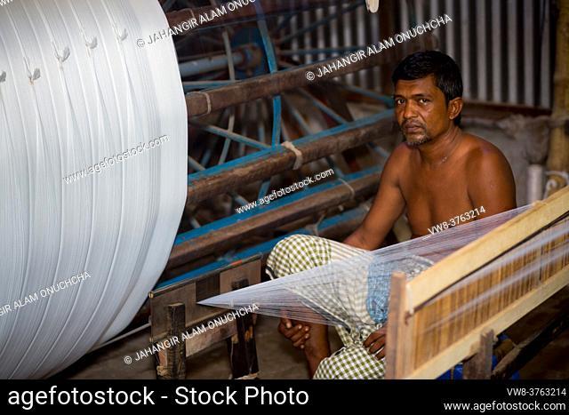 A factory worker makes white yarn spools for making clothes at Narsingdi, Bangladesh
