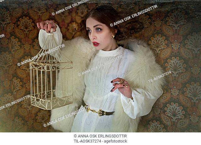 Young woman wearing white dress and fur coat holding a small empty bird cage