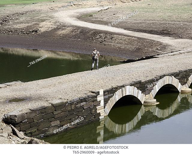 Old bridge submerged throughout the year, of an affluent of the Miño River, in the Belesar reservoir in Portomarin, Lugo. Galicia, Spain
