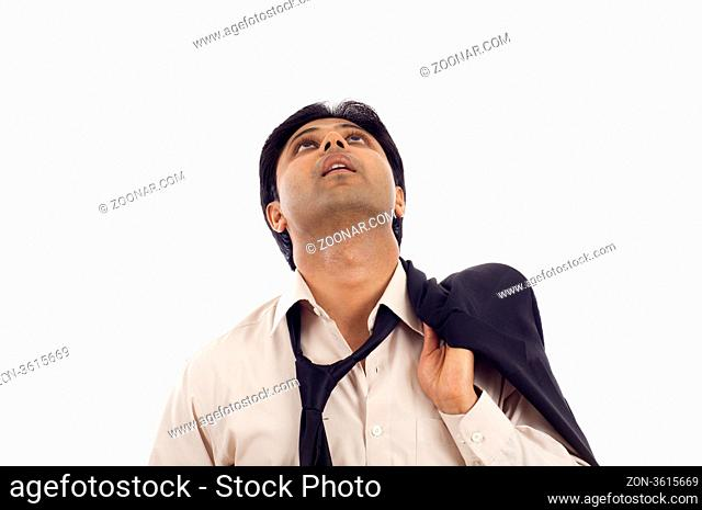 Tired thougful young Indian businessman looking up at copyspace isolated over white background