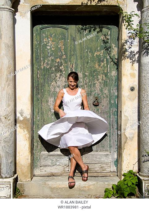 Italy, Ravello, Woman standing in front of watered wooden door, wind blowing woman's dress
