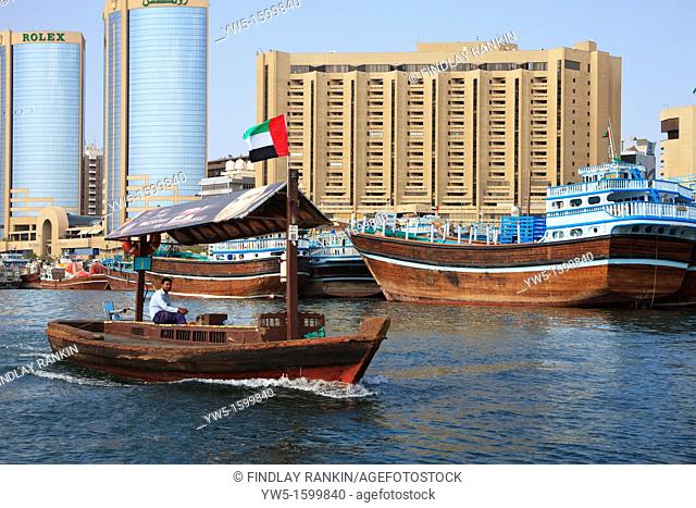 Traditional water taxi, Abra, sailing on the Dubia Creek, in the district of Deira, Dubai, UAE, with traditional Arab dhows tied up at the harbour