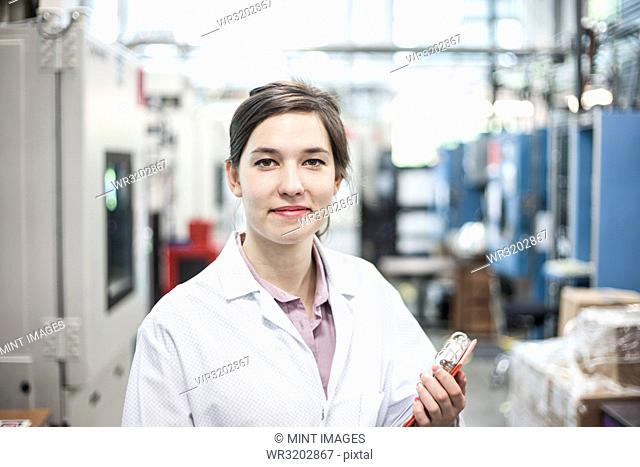 A portrait of a Caucasian female technician in a technical research and development site