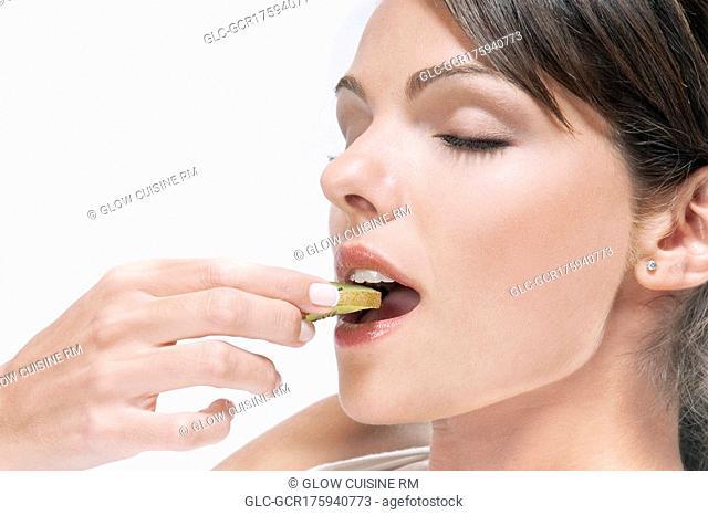 Woman eating a slice of kiwi fruit