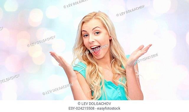 emotions, expressions and people concept - surprised smiling young woman or teenage girl over holidays lights background