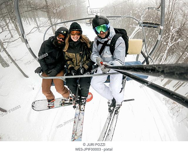 Italy, Modena, Cimone, portrait of happy friends taking a selfie in a ski lift