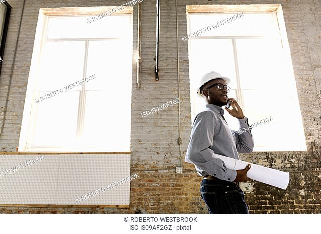 Young interior designer looking at new office space
