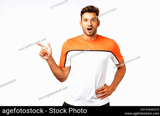 Impressed, surprised good-looking bearded man in sports t-shirt, pointing left, drop jaw and gasping astonished, flushed as discuss impressive goal during...