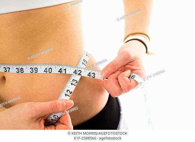 Dieting and body image: A young sporty fit woman 19 year old teenage girl measuring her waist with a tape measure