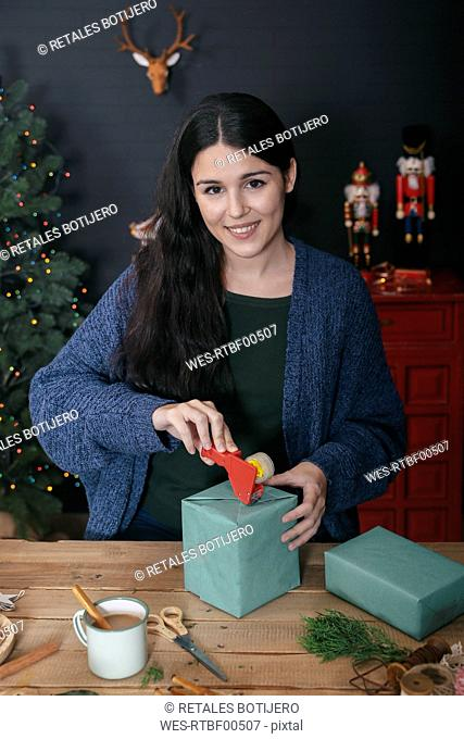 Portrait of smiling young woman wrapping Christmas present