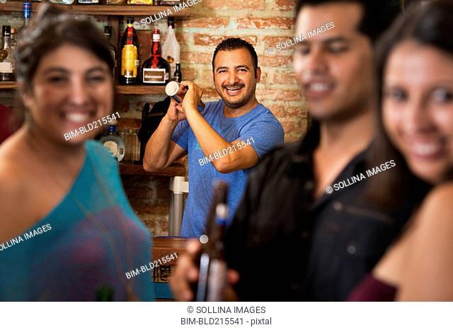 Hispanic bartender making drinks in bar