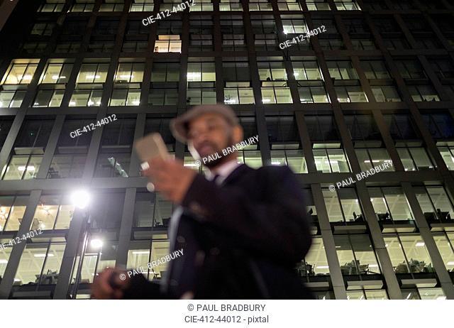 Businessman using smart phone below urban highrise at night