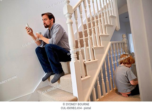 Boy and father sitting on staircase, father reading smartphone texts
