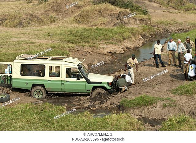 Tourists and tour guides recovery of Jeep Serengeti national park Tanzania