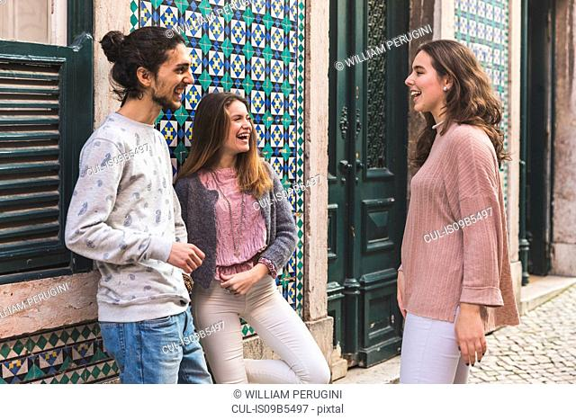 Three friends, standing in street, laughing, Lisbon, Portugal