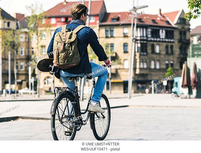 Young man holding skateboard riding bicycle in the city