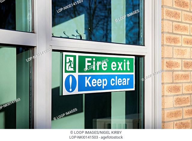 Fire exit and keep clear signs on glass door