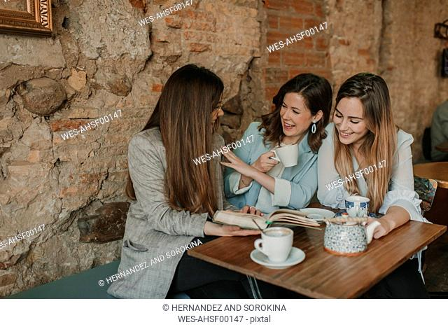 Three happy young women having fun reading a book in a cafe