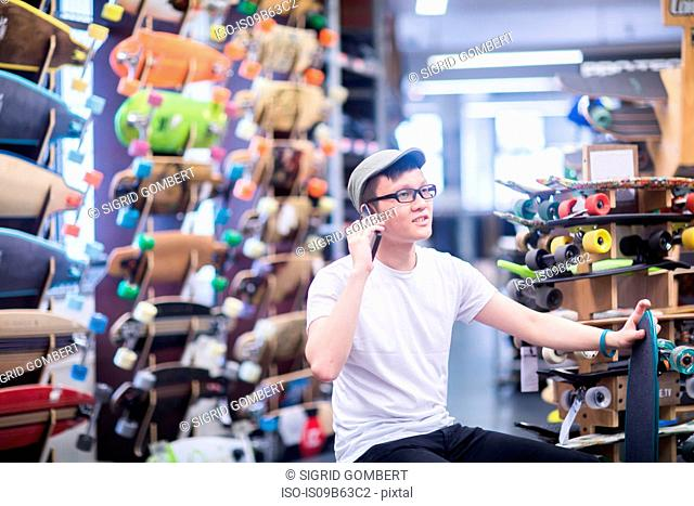 Young male skateboarder making smartphone call in skateboard shop