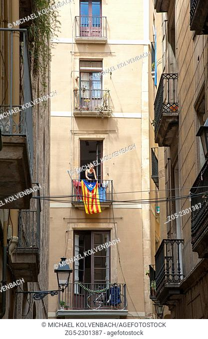 young woman hanging laundry on her balcony draped with Catalan flag in the Gothic Quarter of Barcelona, Catalonia, Spain