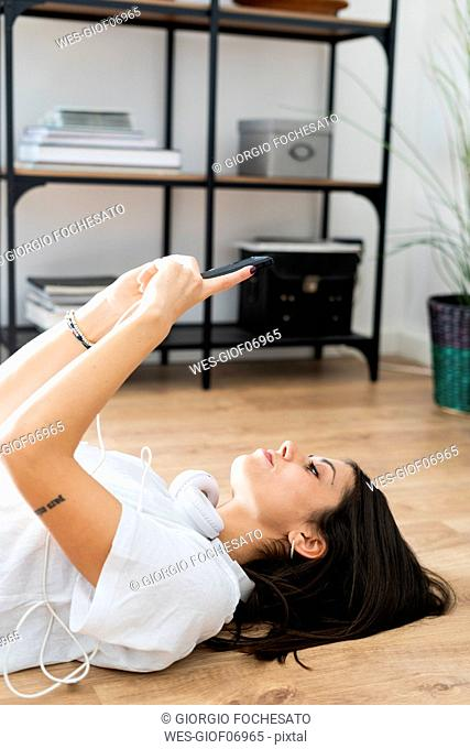 Young woman lying on the floor holding smartphone